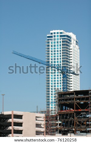 A crane on the top of a new building being erected in the downtown area of a city