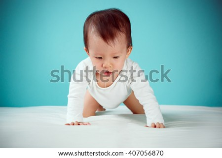 A crawling baby in diaper on bed (soft focus on the eyes)