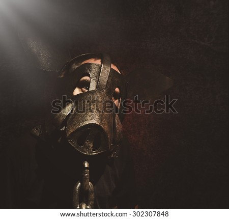 A crazy scary man is wearing a metal pig mask with a chain on a black background for a fear or Halloween concept - stock photo