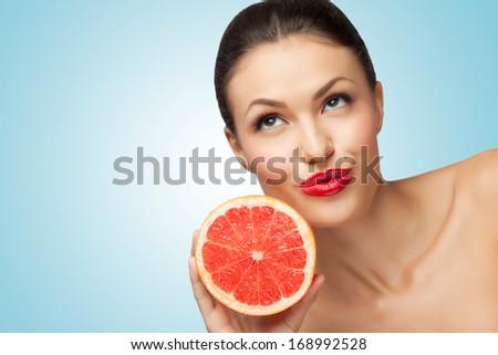 A creative portrait of a beautiful girl holding a fresh ripe grapefruit. - stock photo
