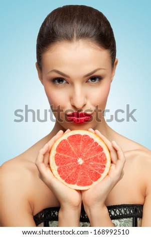 A creative portrait of a beautiful girl holding a red grapefruit sexually under her chin. - stock photo