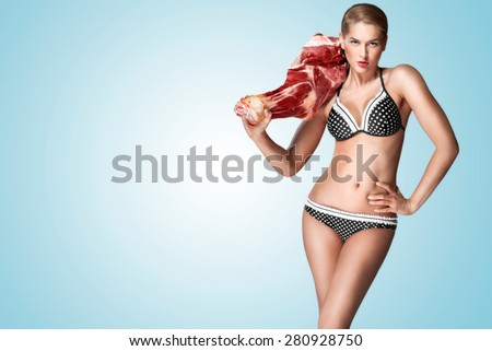 A creative portrait of a beautiful girl in bikini holding raw meat on her shoulder. - stock photo