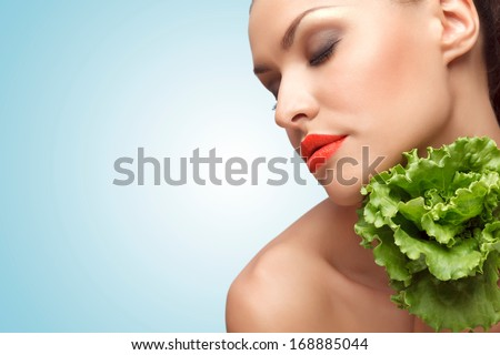 A creative portrait of a beautiful sexy girl on a diet holding with love healthy green lettuce. - stock photo