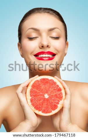 A creative portrait of a beautiful smiling woman squeezing a red grapefruit in her hands. - stock photo