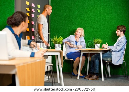 A creative session, with a small project team, with various colored sticky notes on a wall, containing ideas and solution. A woman looks over her shoulder at teamwork taking place behind her. - stock photo