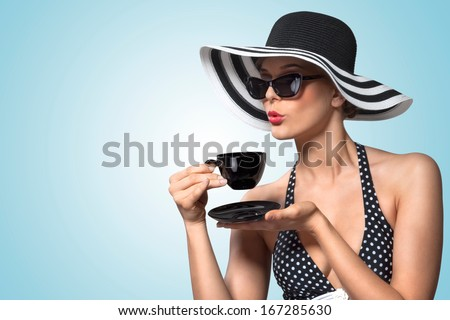 A creative vintage photo of a beautiful pin-up girl drinking tea and showing good table manners. - stock photo