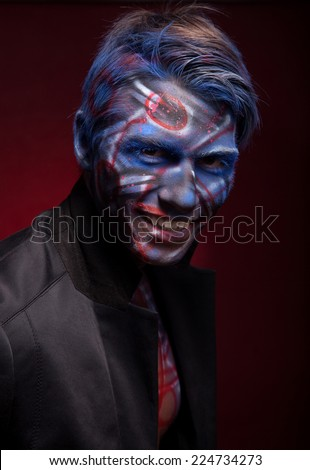 A creepy portrait of a halloween man with bloody body art and face art.