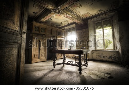 A creepy scenery, this old table creating a moody atmosphere along with the magnificent light. - stock photo