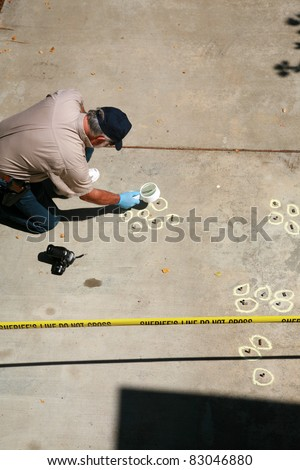 a Crime Scene Investigator gathers evidence at the scene of a crime. Real Sheriff Crime Scene tape helps make this image authentic.
