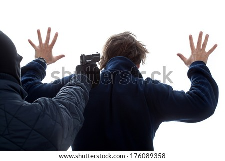A criminal threatening an innocent man with his hands up - stock photo