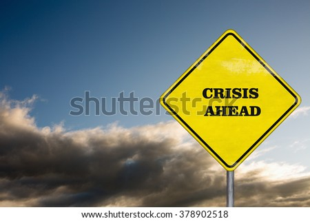 A crisis ahead road sign on a dramatic sky - stock photo