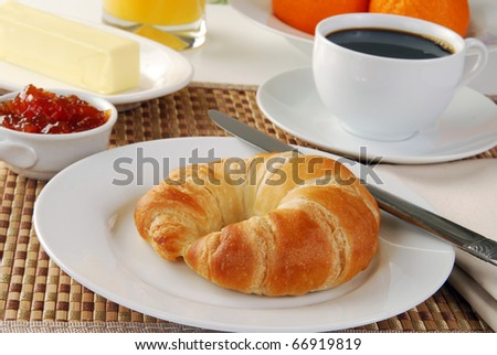 A croissant with coffee, oranges and jam - stock photo