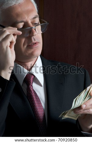 A crooked looking man counting a handful of dollar bills