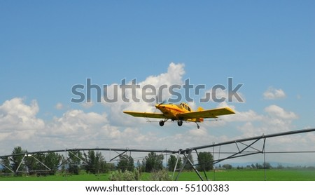 A crop duster finishes a pass down a field as it climbs over a farmer's irrigation system. - stock photo