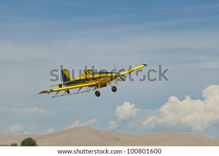 A crop duster finishes a pass with sand dunes in the background.
