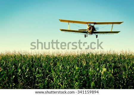 A crop duster flies low over a field of corn in rural Wisconsin. - stock photo