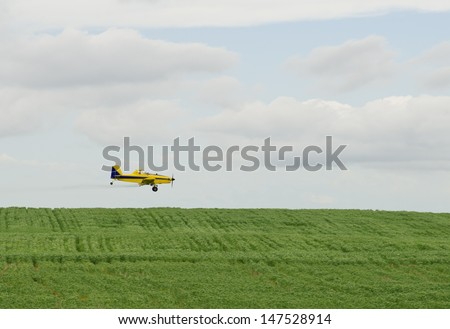 A crop duster spraying a filed - stock photo