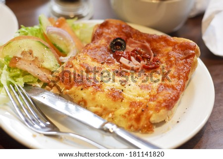 A croque monsieur sandwich with a side salad