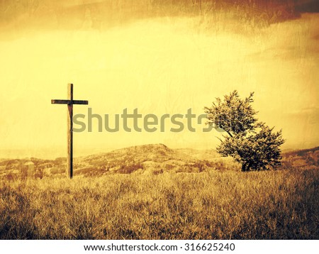 A cross and a bush tree on a mountain meadow with clouded sky behind. On a grungy wall background with copy space available. - stock photo