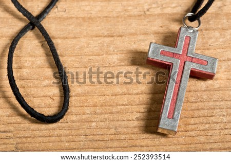 a cross on the old wooden desk - stock photo