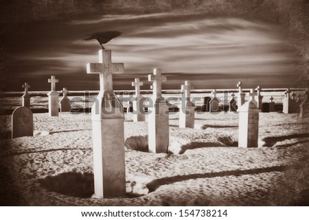 A crow pearches on a tombstone in a dark cemetery. - stock photo