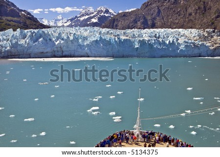 A crowd gathers at the bow of a cruise ship as it approaches a glacier on the  Alaska coast in Glacier Bay. - stock photo