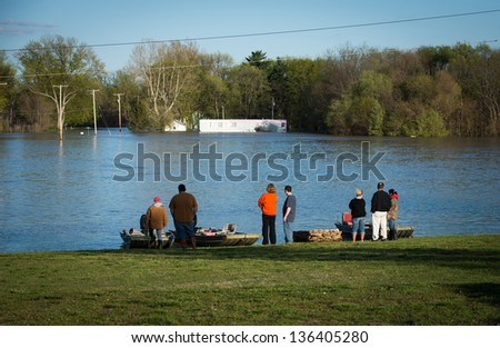 A crowd looks over the waters of the Wabash River that flooded the small town of York, Illinois, after heavy rains - stock photo