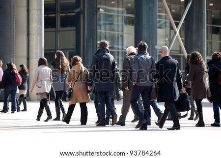 A crowd moving against a background of an urban landscape.