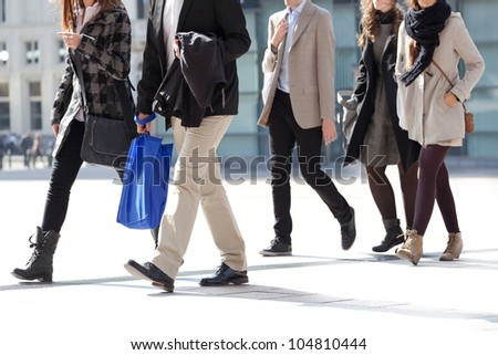A crowd moving against a background of an urban landscape. Young people. Motion blur. Walking businessmen against a background of an urban landscape. - stock photo
