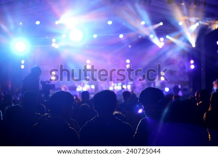 a crowd of cheering fans during a live concert - stock photo