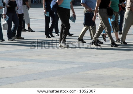 A crowd of pedestrians moving along the sidewalk - stock photo
