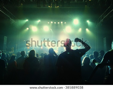 a crowd of people at a concert with a slight blur toned with a retro vintage instagram filter effect - stock photo