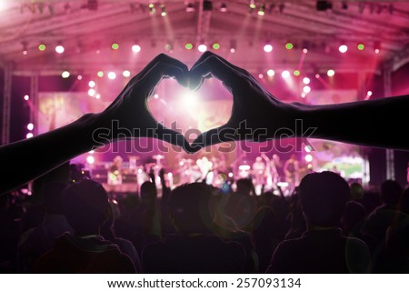 a crowd of people at during a concert with a heart shaped hand shadow male and female - stock photo