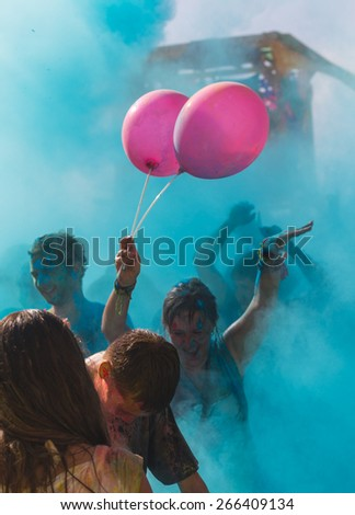 a crowd of people dancing on a colorful festival of colors - stock photo