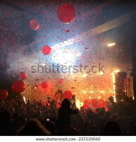 A crowd of people with red balloons, confetti, and bright lights. - stock photo
