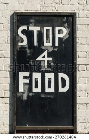 A crude street sign advertising fast food. - stock photo