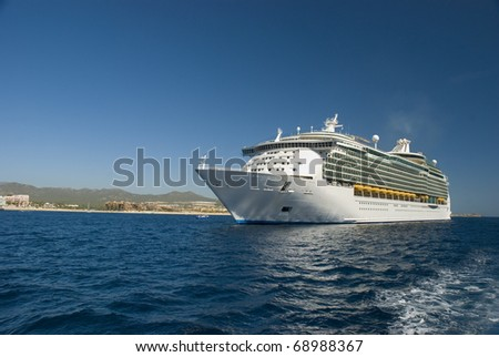 A Cruise ship docked in Cabo San Lucas, Mexico. The beach and condominiums are in the background. - stock photo
