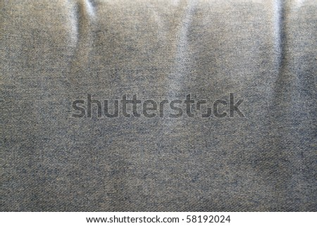 A crumple stained blue jeans material surface as textural background.