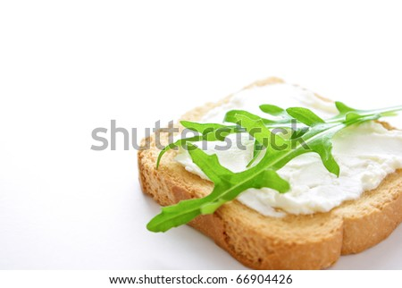 A crusty toasted bread with cheese and rocket salad leaves isolated on a white background