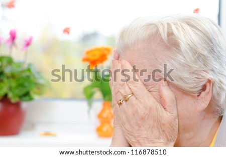 A crying elderly woman covering her face - stock photo