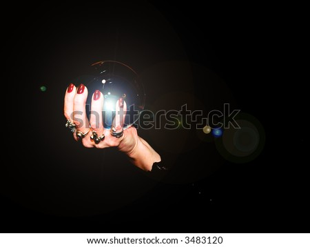 A crystal ball is held in the hands of a fortune teller. - stock photo