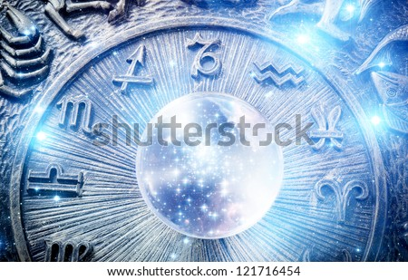 a crystal ball with stars over zodiac background - stock photo