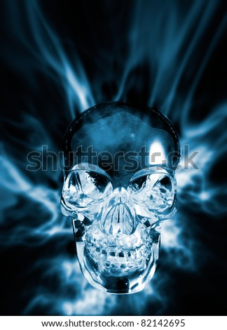 A crystal skull shown against an atmospheric light effect backdrop - stock photo