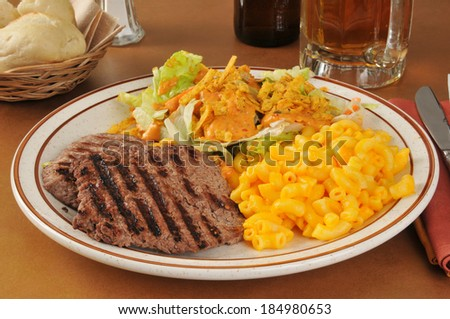 A cube steak dinner with macaroni and cheese and a salad