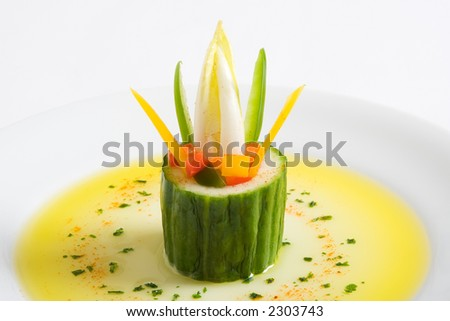 A cucumber vegetarian starter with olive oil on a white plate