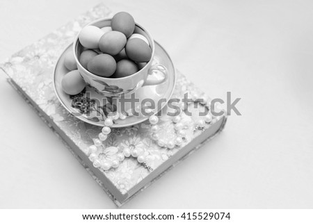 A cup and saucer with painted easter eggs and pearls on the book on white background