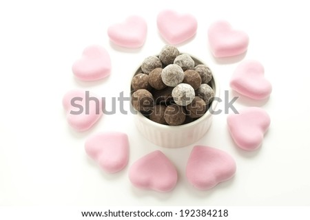 A cup filled with chocolate truffles surrounded by ten pink hearts. - stock photo