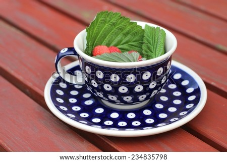 A cup from polish pottery in Boleslawiec with raspberries/A cup from polish pottery in Boleslawiec with raspberries - stock photo