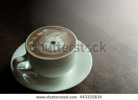 A cup hot cocoa with flower from milk foam and chocolates. A cup hot cocoa dark style. A cup hot cocoa Was decorated with chocolates on wooden table - stock photo