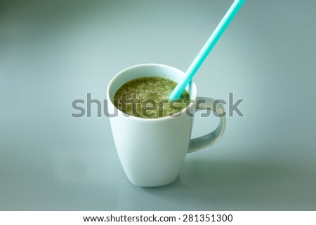 A cup of a green smoothie with a blue straw inside, healthy drink and food that fits for a diet